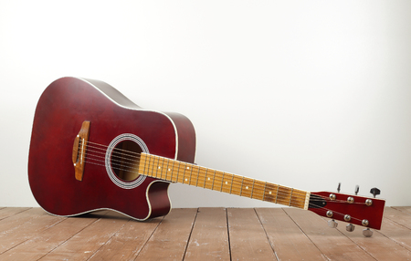 Musical instrument - Classic acoustic guitar on a white wall background and wooden floor. Imagens