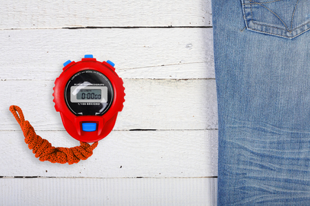 Mans concept sport set - blue jeans and Red Stopwatch on a wooden background. Imagens