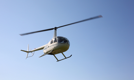 The aircraft - White helicopter makes flight at low height.