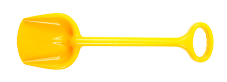 Tools Building and repair - Yellow toy shovel with a handle on a white background. It is isolated, the worker of paths is present.