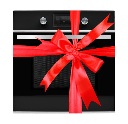 The electric oven gift tied red bow on a white background. It is isolated, the worker of paths is present.