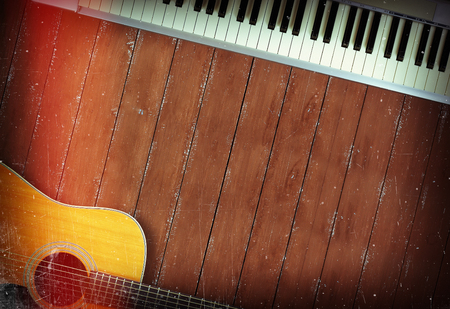 Musical instrument - Sloseup MIDI piano 61 key keyboard and acoustic guitar on a wooden background Imagens