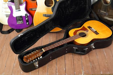 Musical instrument - Vintage twelve-string acoustic guitar hard case on a guitar and wooden background.