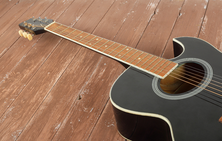 Musical instrument - Fragment black cutaway acoustic guitar on a wood background.