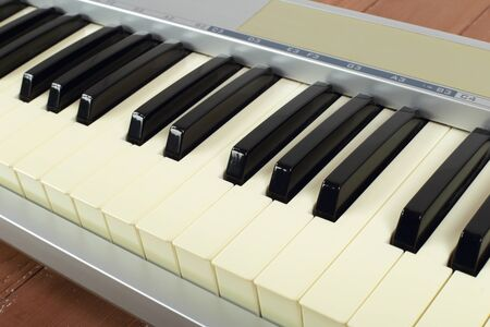 Musical instrument - Sloseup fragment MIDI piano 61 key keyboard on a wooden background