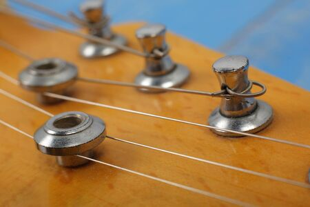 Musical instrument - Fragment headstock peghead neck tuning peg electric guitar on a blue wood background.