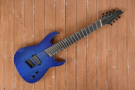Musical instrument - Blue 8-srtings guitar on a wooden background. Stock Photo