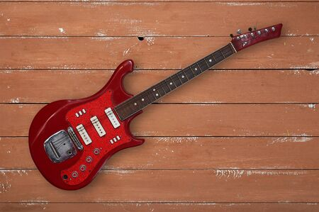 Musical instrument - Red retro guitar on a wooden background.