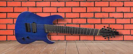 Musical instrument - Blue 8-srtings guitar on a red brick wall background and wooden floor.