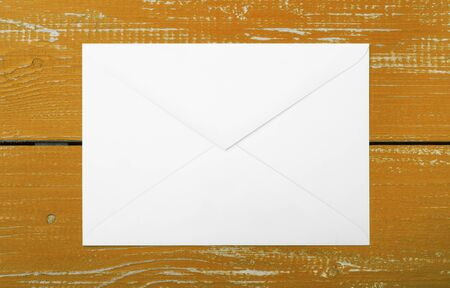 Postage and packing service - Envelope on a brown wood plank background. Stock Photo