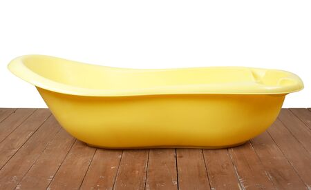 Motherhood  and hygiene - Yellow children bath on a white and wooden background