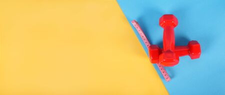 Two red dumbbell and Measuring tape centimeters on a yellow background and a on a blue gymnastic rug.