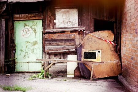 Microwave Oven on a bench against the background of slums ruins of the shed and walls. Stock Photo - 128715094