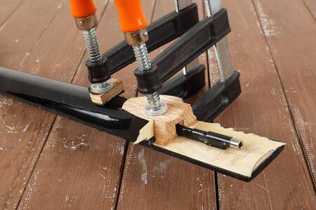 Guitar repair and service - Closeup Clamping a guitar neck wooden background Stock fotó