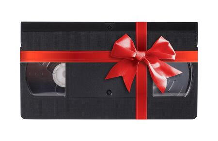 Old, obsolete video cassette vhs gift tied red bow on a white background. Isolated 免版税图像