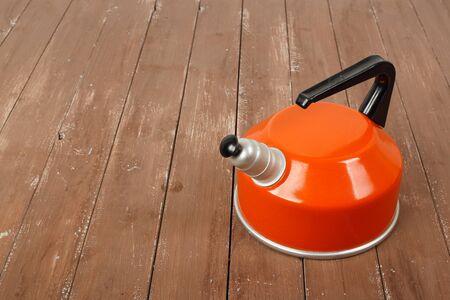 Kitchen utensils - Orange whistling kettle on a wooden background