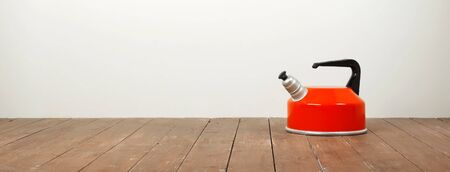 Kitchen utensils - Orange whistling kettle on a white and wooden background Stockfoto