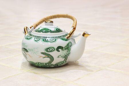Kitchen utensils - Small Vintage porcelain teapot closeup.