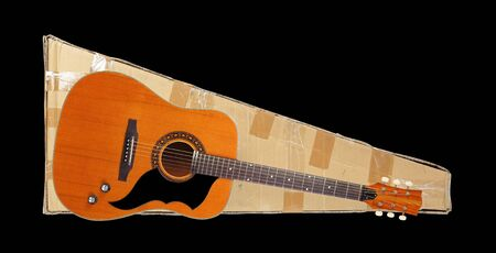 Postage and packing service, Music and sound - Purchase Acoustic vintage guitar and package on a black background. Isolated.