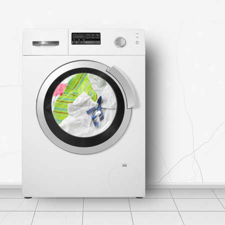 Major appliance - Washing machine washing of clothes in home interier on a light wall background.