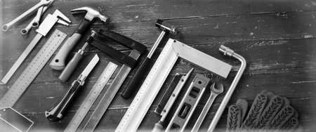 Closeup tools building and repair set on a vintage wooden background monochrome