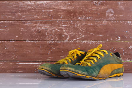 Clothes shoes and accessories - Old pair green and yellow sneakers wooden background with reflection