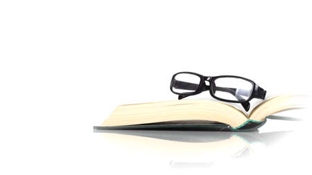 Science and education - Spectacles on the open book white background with reflection