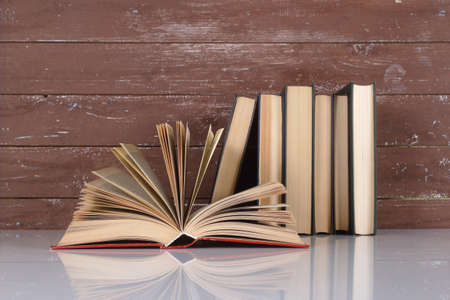 Science and education - Open book on a group books and wooden background. With reflection