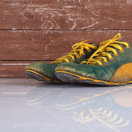 Clothes shoes and accessories - Closeup old pair green and yellow sneakers wooden background with reflection