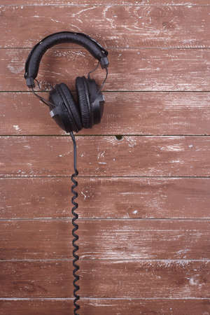 Musical equipment - Black headphone on a wood background.