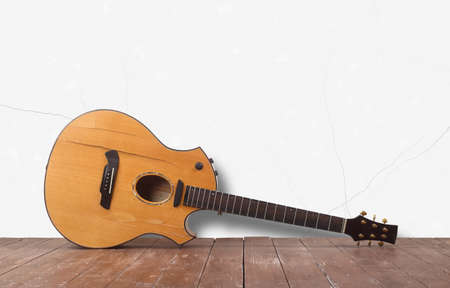 Musical instrument - Front view broken acoustic guitar on a white wall background and wooden floor.