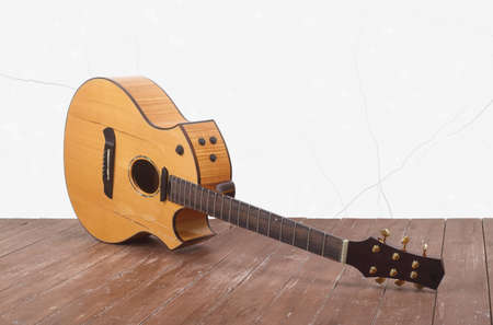 Musical instrument - Broken acoustic guitar on a white wall background and wooden floor.
