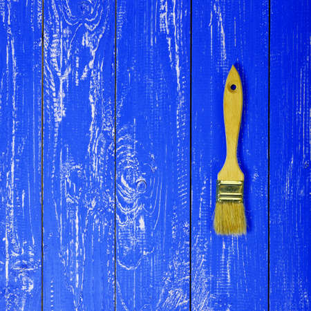 Construction, repair, tools - Paintbrush on a dark blue wooden plank background Reklamní fotografie