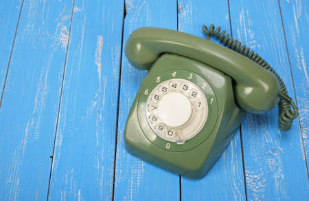 Vintage Phones - Green a retro telephone on a blue wood background.