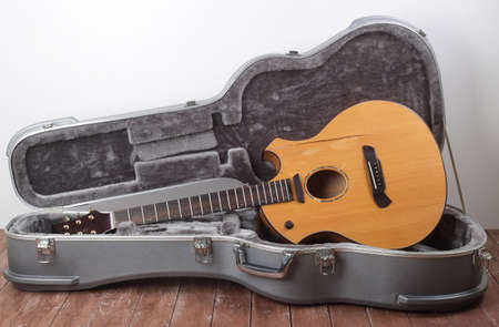 Musical instrument - Broken acoustic guitar in hard case on a white wall background and wooden floor.