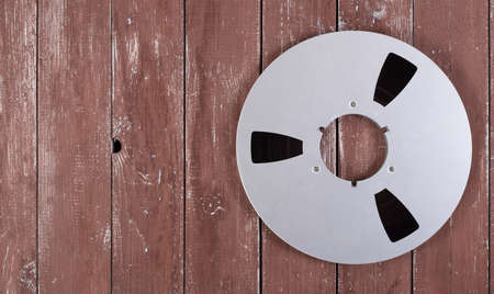 Music and sound - Front view Closeup fragment 265 mm Aluminum reel Magnetic tapes for nab on a wooden background.