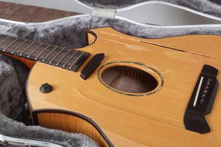Musical instrument - Closeup fragment Broken acoustic guitar in hard case
