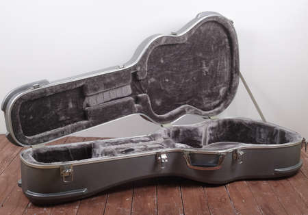 Musical instrument - Open silver acoustic guitar hard case on a wooden and white background Reklamní fotografie