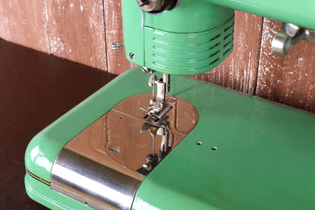 Household appliances - Closeup fragment old retro green sewing machine wooden background