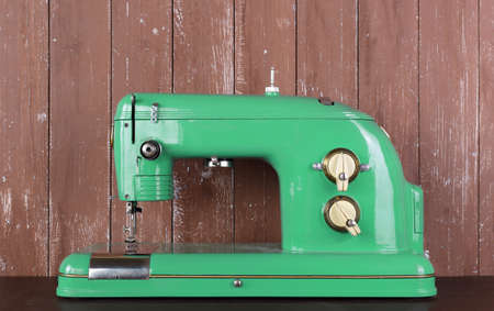 Household appliances - Front view old retro green sewing machine wooden background Reklamní fotografie
