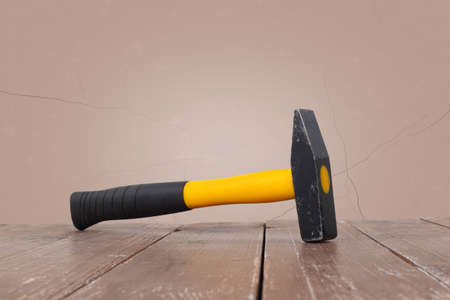 Tools Building and repair - Big hammer on a wooden and brown wall background.
