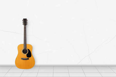 Home interior - Classic vintage acoustic guitar in front on a white wall background Reklamní fotografie