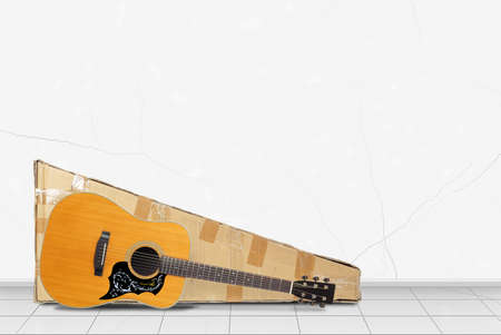 Home interior - Classic vintage acoustic guitar and package in front on a white wall background