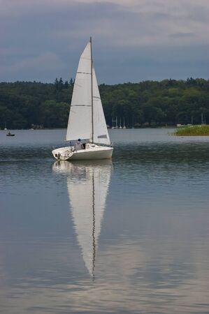 lakeland: Sailboat ON THE LAKE. Sailor sailboat floating on the lake. Image sailboats reflected in water lake unheard he Lubuskie Lakeland. Stock Photo