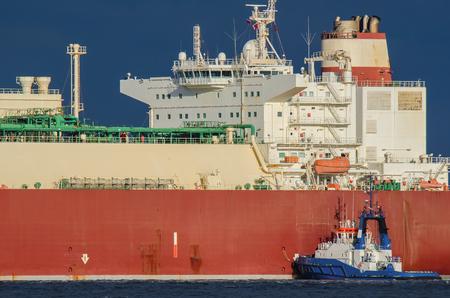 SWINOUJSCIE. Small tugboat helps to moor at the quay big lng tanker Standard-Bild
