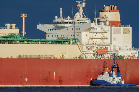 lng: SWINOUJSCIE. Small tugboat helps to moor at the quay big lng tanker Stock Photo