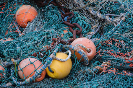 catena: TANGLET FISHING NETS. Buoys and tangled fishing nets lie on the waterfront fishing port Stock Photo
