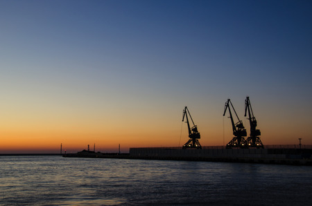is cloudless: SEA PORT OF GDYNIA AT DAWN. Cloudless sky, harbor cranes and a quay at the port of Gdynia at dawn