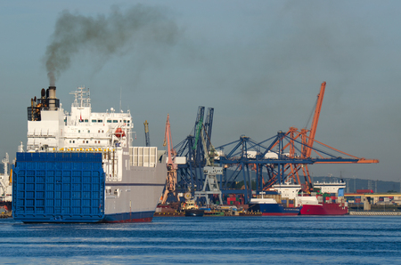 Gdynia - VESSELS IN PORT. Large ship entering the port of Gdynia, the waterfront dock container