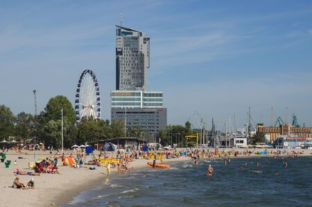 devilish: Gdynia - CITY BEACH. City residents and tourists lounging on a beach city Editorial